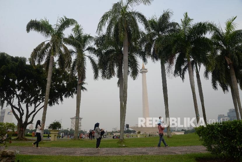 Warga mengunjungi kawasan Monumen Nasional (Monas) di Jakarta, Ahad (23/4).