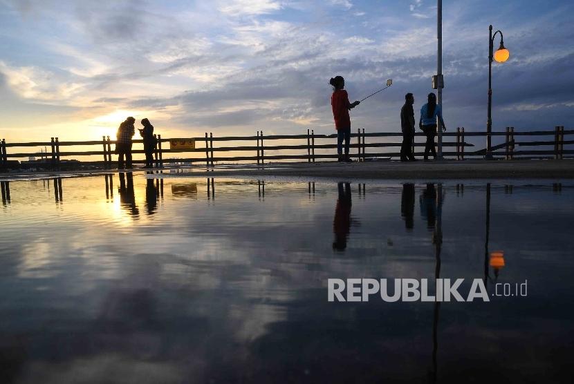Warga menikmati matahari tenggelam saat menunggu berbuka puasa (ngabuburit) di Pantai Festival, Ancol, Jakarta, Kamis (30/6).  (Republika/Agung Supriyanto)