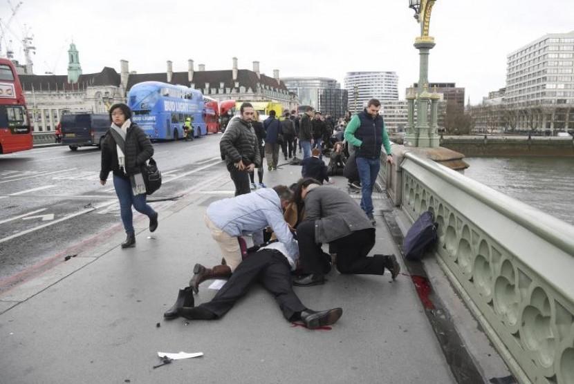 Warga menolong korban terluka di Westminster Bridge, London, Rabu (22/3). Lima orang tewas dan 40 luka dalam serangan di parlemen Inggris.