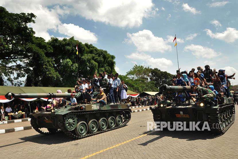 Warga menunmpang kendaraan tempur saat defile alutsista TNI pada Upacara Peringatan HUT TNI ke-72 di lapangan Panglima Besar (Pangsar) Jendral Sudirman, Ambarawa, Kabupaten Semarang, Kamis (5/10).