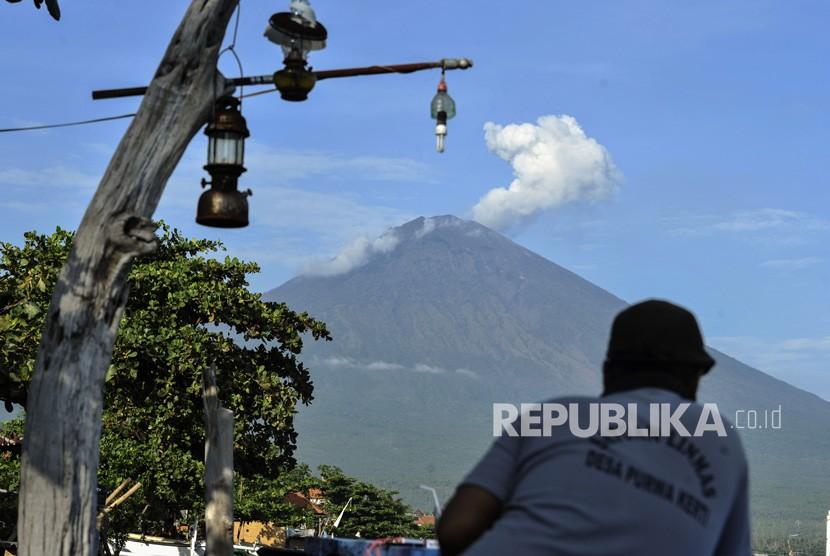 Warga menyaksikan asap putih yang terhembus dari kawah Gunung Agung terlihat dari Amed, Karangasem, Bali, Kamis (7/12).