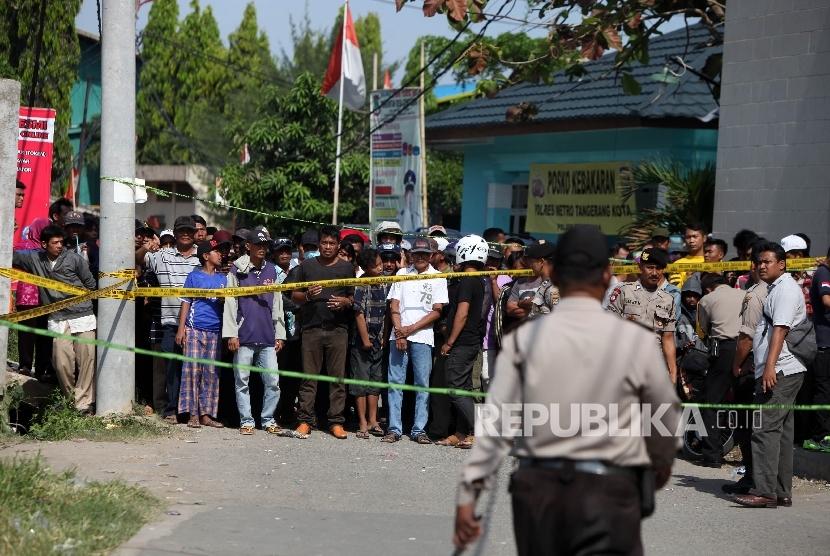Warga menyaksikan saat petugas kepolisian melakukan olah TKP di lokasi pasca ledakan di pabrik produksi kembang api, Jalan Salembaran, Desa Belimbing, Kecamatan Kosambi Kabupaten Tangerang, Banten, Jumat (27/10).