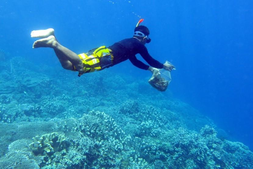 Warga menyelam untuk mengambil sampah di terumbu karang taman laut. ilustrasi