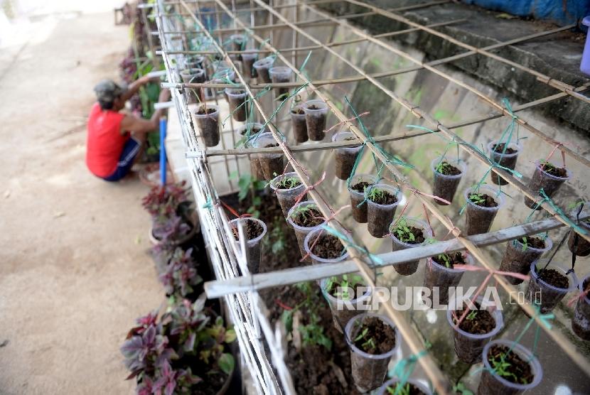 Warga menyiapkan tempat menanam tanamanhiasdi tepi Kali Ciliwung, Kawasan Raden Saleh, Jakarta Pusat, Selasa (6/12).