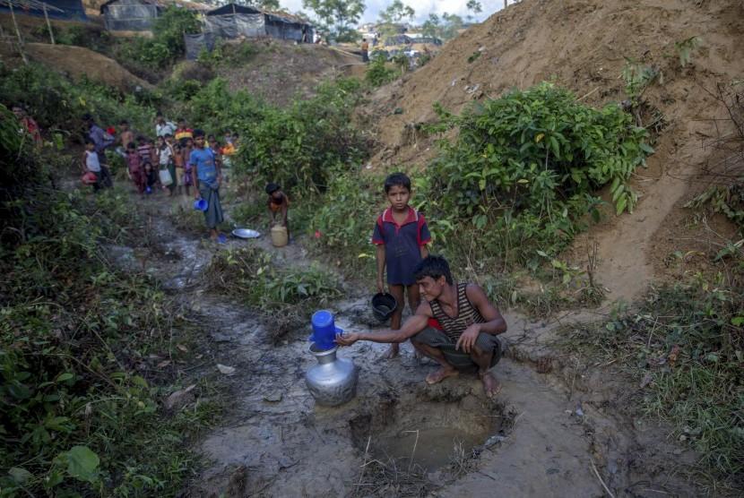 Warga Muslim Rohingya, yang menyeberang dari Myanmar ke Bangladesh, mengumpulkan air hujan di kamp pengungsi Balukhali, Bangladesh, Rabu (13/9).