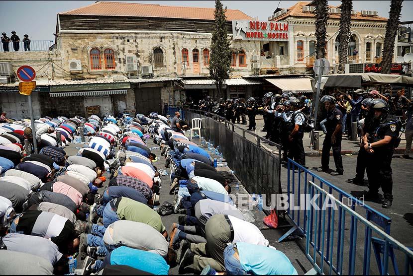 Warga Palestina melaksanakan Shalat Jumat di jalan menuju kompleks Masjid Aqsha yang diblokir polisi Israel di Kota Tua Yerusalem.