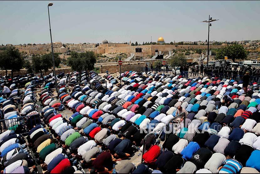 Warga Palestina melaksanakan Shalat Jumat di jalan menuju kompleks Masjid Aqsha yang diblokir polisi Israel di Kota Tua Yerusalem, Jumat (21/7)