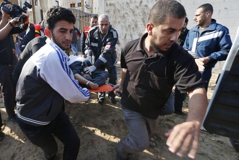 Warga Palestina mengevakuasi seorang pria yang terluka setelah Israel melakukan serangan udara di Jalur Gaza pada Kamis (15/11). Jumlah korban di pihak Palestina mencapai 13 orang dan tiga orang dari pihak Israel, sehingga ancaman serangan habis-habisan ol
