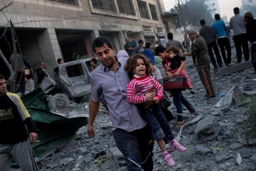 Warga Palestina meninggalkan rumah mereka yang hancur diserang Israel, di dekat lapangan Kota Gaza, Senin (19/11).