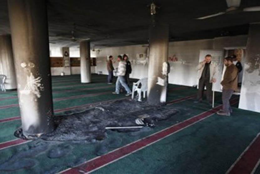 Warga menyaksikan kerusakan yang terjadi akibat pembakaran masjid (Ilustrasi)