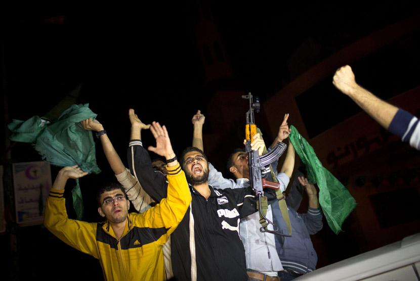 Warga Palestina merayakan kemenangan atas Israel setelah tercapainya kesepakatan gencatan senjata di Gaza, Rabu (21/11) malam.  (AP/Bernat Armangue)