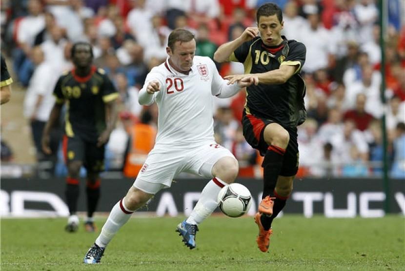 Wayne Rooney (kiri), striker timnas Inggris, berebut bola dengan pemain timnas Belgia, Eden Hazard, dalam laga uji coba di Stadion Wembley, London, Sabtu (2/6).
