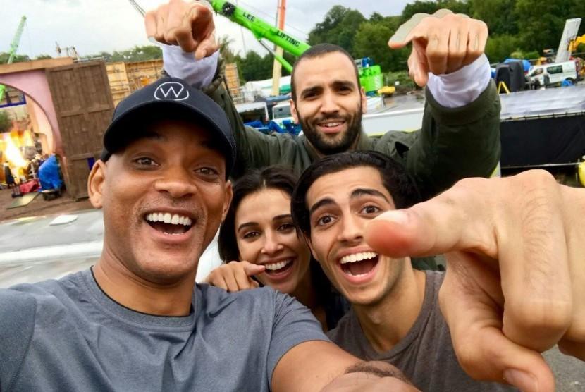 Will Smith bersama dengan pemeran Aladdin lainnya sedang berswafoto.