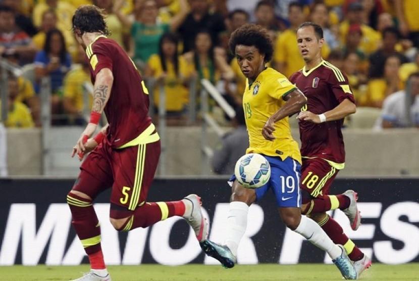 Willian (tengah) dijaga dua pemain Venezuela