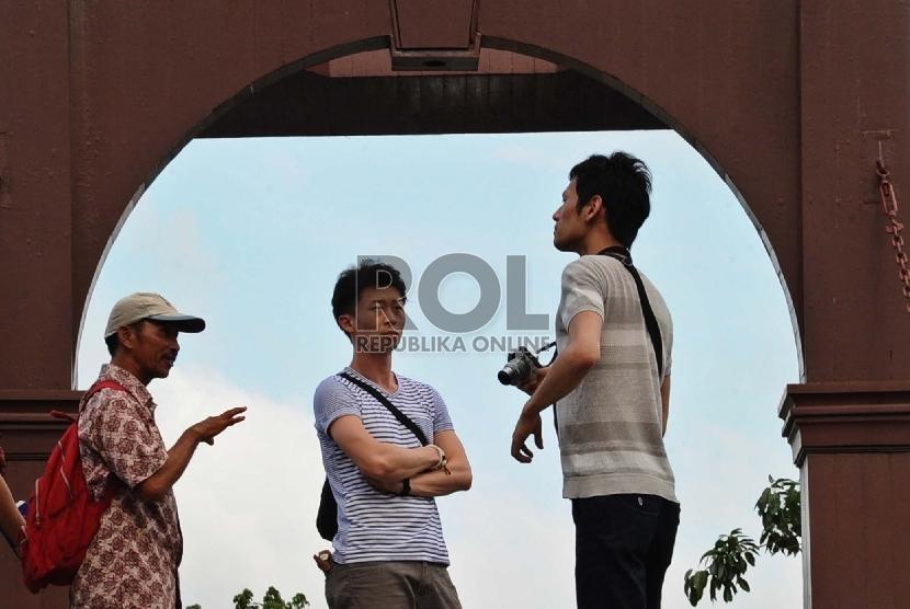 Wisatawan asing mendengarkan penjelasan pemandu wisata di kawasan Kota Tua, Jakarta, Ahad (10/1). (Republika/Tahta Aidilla)