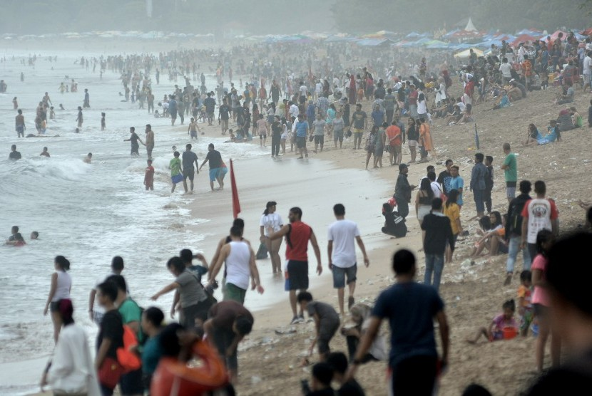 Tourists enjoy holiday season by flocking to Kuta beach, Badung, Bali, on December 31, 2017.