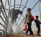 Sejumlah warga melintasi jembatan penyebrangan orang (JPO) tanpa atap di Jakarta, Sabtu (31/3). (Republika/Agung Fatma Putra)