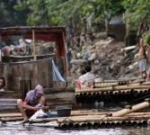 Warga menggunakan MCK darurat di bantaran kali Ciliwung, Bukit Duri, Jakarta, Senin (19/3). (Republika/Adhi Wicaksono)