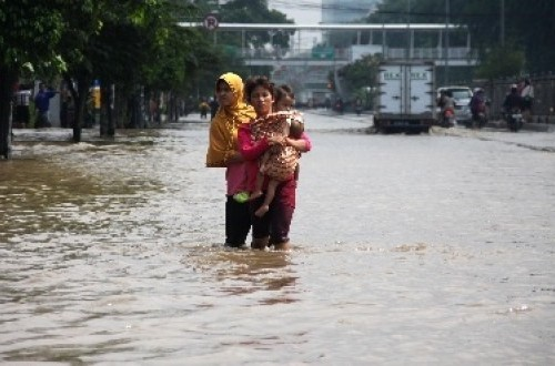 Residents walk through a flooded street. (File photo)