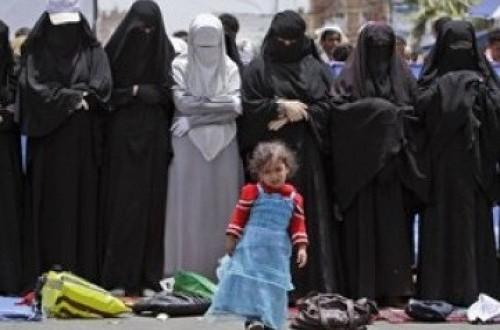 Seorang bocah perempuan berdiri di depan kaum wanita Yaman yang shalat di sela-sela demonstrasi menentang Presiden Saleh.