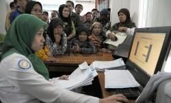 Sejumlah warga antre mendaftar sebagai peserta BPJS Kesehatan di Kantor Pelayanan Askes Sukmajaya, Depok, Jabar.