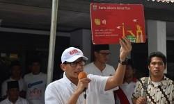 Calon Wakil Gubernur DKI Jakarta Sandiaga Uno menunjukkan Kartu Jakarta Sehat (KJS) kepada warga Joglo, Jakarta Barat, Selasa (28/3).