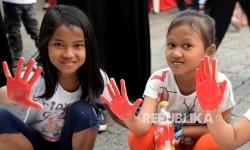 Anak-anak menunjukan tangannya seusai memberikan cap tangan dikain putih dalam kegiatan Cap Telapak Tangan Cinta untuk Rohingya di halaman parkir Sarinah, Jakarta, Ahad (10/9).