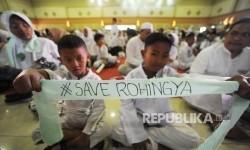 Anak Membentangkan ikat kepala bertuliskan #SaveRohingya dalam acara konser amal peduli muslim Rohingya dan Palestina di Ballroom Bumi Wiyata, Depok, Kamis (21/9).
