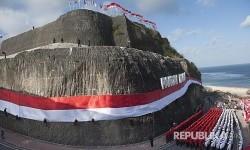 Anggota Brimob Polda Bali dan Basarnas mengibarkan Bendera Merah Putih di dinding tebing Pantai Pandawa, Badung, Bali, Senin (14/8).