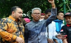 Buni Yani mengepalkan tangan usai sidang eksepsi dirinya, di Gedung Perpustakaan dan Arsip Daerah, Kota Bandung, Selasa (11/7).