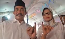 Calon Bupati Tunggal Haryanto (kiri) beserta istri Musus Indarwani menunjukkan jari yang bertinta seusai menggunakan hak suara di Desa Kraci, Batangan, Pati, Jawa Tengah, Rabu (15/2).