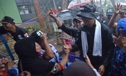 Calon Gubernur DKI Jakarta Agus Harimurti Yudhoyono (kanan) menyapa warga ketika mengunjungi Kompleks UKA, Tugu Utara, Jakarta, Senin (16/1).