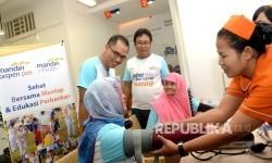 Direktur Utama Bank Mantap Josephus K Triprakoso (kanan atas) bersama Direktur Utama Mandiri Inhealth Iwan Pasila (kiri) melihat nasabah melakukan konsultasi kesehatan di kantor cabang Bank Mantap, Jakarta, Jumat (19/5).