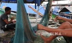 Dua orang nelayan memperbaiki jaring penangkap ikannya yang robek dan terkoyak di kampung nelayan Cilincing Jakarta, Kamis (12/1).