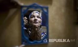 Hajjah Dalal (43) berdoa di kediamannnya sebelum membangunkan warga setempat bangun sahur di Distrik Ard Besari, Kairo, Mesir.