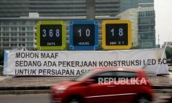 Kendaraan melintas disamping layar digital hitung mundur pelaksanaan Asian Games 2018 di Kawasan Bundaran HI, Jakarta, Senin (14/8).