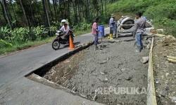 Pekerja memperbaiki jalur alternatif Jalan Lingkar Kamojang, Kabupaten Bandung, Senin (12/6).