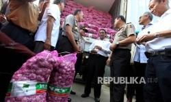 Menteri Pertanian Amran Sulaiman bersama dengan Kementerian Perdagangan dan Polri menyambut 2 kontainer bawang putih yang diimpor langsung dari China pada Operasi Pasar Bawang Putih di Pasar Induk Kramat Jati, Jakarta, Rabu (17/5).