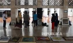 Panitia memasang kaligrafi untuk mempersiapkan pameran di Masjid Istiqlal, Jakarta, Ahad (19/2).