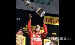 Pebalap Ferrari Sebastian Vettel merayakan kemenangannya pada Grandprix Hongaria di Sirkuit Hongaroring, Hongria, Ahad (30/7).