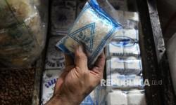 Pedagang menunjukan garam di pasar.