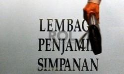 Pekerja melintas saat melakukan aktifitas di kantor Lembaga Penjamin Simpanan (LPS), Jakarta.