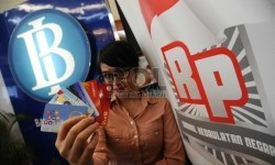 Pekerja memperlihatkan kartu e-money berlogo Gerakan Nasional Non Tunai (GNNT) 'Cinta Non-Tunai, Cinta Rupiah' di pusat perbelanjaan, Jakarta, Kamis (19/11).  (Republika/Tahta Aidilla)