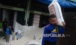 Pekerja mengangkat karung beras di Pasar Induk Beras Cipinang, Jakarta Timur, Kamis (13/4).