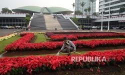 Pekerja menyiram bunga yang sudah ditanam di halaman gedung kura-kura di Kompleks Parlemen, Senayan, Jakarta, Senin (14/8).