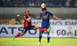 Pemain Persib Bandung Dedi Kusnandar (biru) menyundul bola dibayangi pemain Persipura Ricardo Salampessy.
