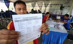 Pemudik menunjukkan formulir pendaftaran angkutan gratis untuk sepeda motor di Stasiun Pasar Senen, Jakarta, Selasa (21/6).