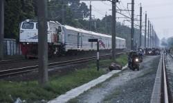 Pengendara motor melintas di dekat rel kereta api di Kawasan Buaran, Jakarta.