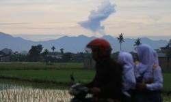 Pengendara sepeda motor melintas dengan latar belakang Gunung Sinabung menyemburkan material vulkanik tampak dari kawasan Sunggal (70 km dari Sinabung), Deli Serdang, Sumatera Utara, Selasa, (19/7).