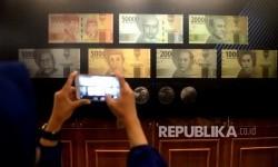 Pengunjung memotret uang Rupiah baru usai peresmian pengeluaran dan pengedaran uang Rupiah Tahu Emisi 2016 di Bank Indonesia, Jakarta, Senin (19/12).